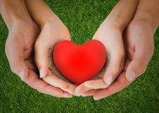 Couple holding heart shape in cupped hands Royalty Free Stock Photos