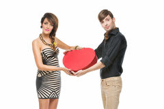 Couple holding heart shaped box. Young beautiful couple looking like dools holding big red heart shaped box Royalty Free Stock Images