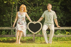 Couple holding heart shaped chalkboard Royalty Free Stock Photo