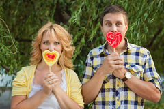 Couple holding heart shaped lollipops Royalty Free Stock Photos
