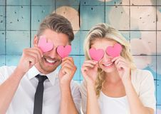 Couple holding hearts over eyes Royalty Free Stock Photos