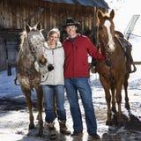 Couple holding horses. Stock Photos