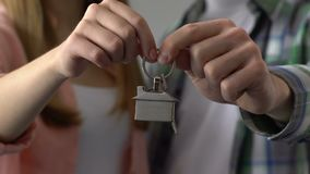 Couple holding key chain house, buying property, mortgage for young family