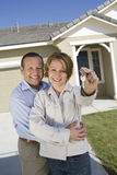 Couple Holding Key In Front Of New House. Portrait of happy mature couple holding key in front of new house Royalty Free Stock Image