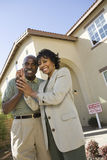 Couple Holding Key In Front Of New House Royalty Free Stock Photos