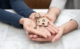 Couple holding key of their new house together. Happy Young couple holding key of their new house on white marble table together Royalty Free Stock Images