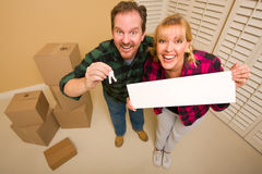 Couple Holding Keys and Blank Sign with Boxes Royalty Free Stock Photography