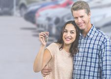 Couple Holding Keys with cars. Digital composite of Couple Holding Keys with cars Stock Photos