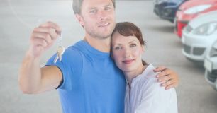 Couple Holding Keys with cars. Digital composite of Couple Holding Keys with cars Stock Image