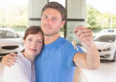 Couple Holding Keys with cars. Digital composite of Couple Holding Keys with cars Royalty Free Stock Photography