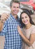 Couple Holding Keys with cars. Digital composite of Couple Holding Keys with cars Royalty Free Stock Photo