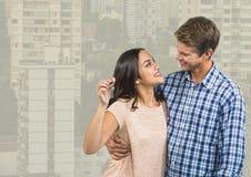Couple Holding Keys with city high rises. Digital composite of Couple Holding Keys with city high rises Stock Image