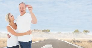 Couple Holding Keys with road. Digital composite of Couple Holding Keys with road Royalty Free Stock Photos