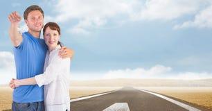 Couple Holding Keys with road. Digital composite of Couple Holding Keys with road Royalty Free Stock Photo