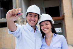 Couple holding keys to their house Royalty Free Stock Photography