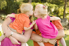 Couple Holding Kissing Brother and Sister Toddlers. Mom and Dad Holding Kissing Brother and Sister Toddlers in the Park Stock Images