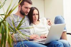Couple holding laptop Stock Image