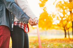 Couple holding leash together in autumn park Royalty Free Stock Photography
