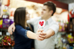 Couple holding lollipop in their hands. Supermarket: couple holding lollipop in their hands Stock Image