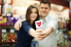 Couple holding lollipop in their hands. Supermarket: couple holding lollipop in their hands Royalty Free Stock Photo