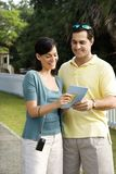 Couple holding map and smiling. Royalty Free Stock Photos