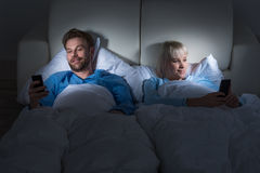 Couple Holding Mobile Phones In Bedroom Stock Photos