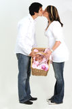 Couple holding new baby in basket while kissing Royalty Free Stock Image