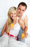 Couple holding orange juice glasses in bed Stock Photo