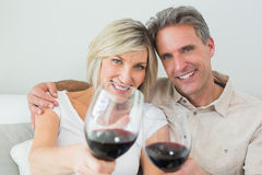Couple holding out wine glasses at home Stock Image