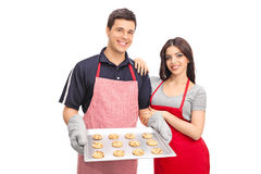 Couple holding a pan with chocolate chip cookies Royalty Free Stock Images