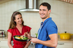 Couple holding pan of vegetables and smiling Stock Images