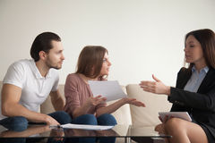 Couple holding papers arguing with agent or banker about fraud. Young indignant women sitting next to men indoors holding documents arguing with female agent or royalty free stock photos