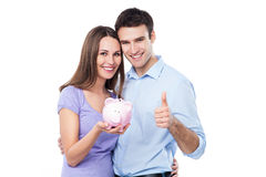 Couple holding piggy bank and showing thumbs up Royalty Free Stock Images