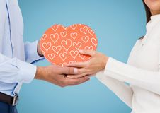 Couple holding pink heart shape box against blue background Royalty Free Stock Photos