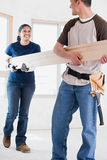 A couple holding a plank of wood Royalty Free Stock Image