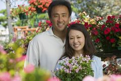 Couple holding plants in plant nursery portrait Stock Images