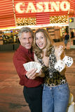 Couple Holding Playing Cards And Dices Against Casino Stock Image