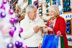Couple Holding Present At Christmas Store Stock Image