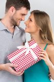 Couple holding present looking at each other. Stock Photography