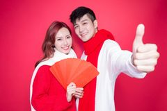 Couple holding red envelope. On the red background Royalty Free Stock Photo
