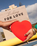 Couple holding red heart in front of love sign Royalty Free Stock Photography