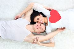 Couple holding red heart together lie in a bed Royalty Free Stock Photography