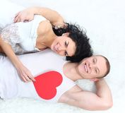 Couple holding red heart together lying Royalty Free Stock Photos