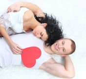 Couple holding red heart together lying Stock Image