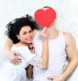 Couple holding red heart together lying in a bed Royalty Free Stock Photography