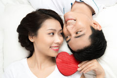 Couple holding red heart together lying Stock Photo