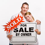 Couple holding for sale sign Royalty Free Stock Photos