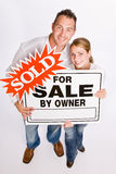 Couple holding for sale sign Royalty Free Stock Photo