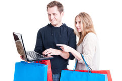 Couple holding shopping bags and looking on laptop Stock Image