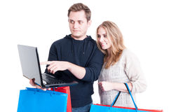Couple holding shopping bags and looking on laptop Royalty Free Stock Photos